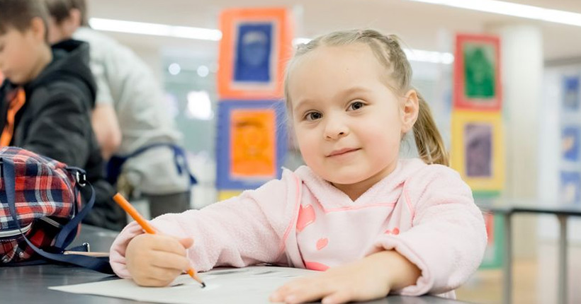 Young girl drawing on paper with pencil