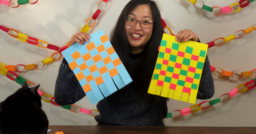 Young woman holding up colorful paper strips woven together