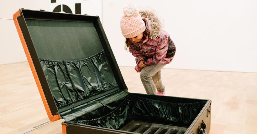 Little girl bending down to look at a suitcase that opens up underground