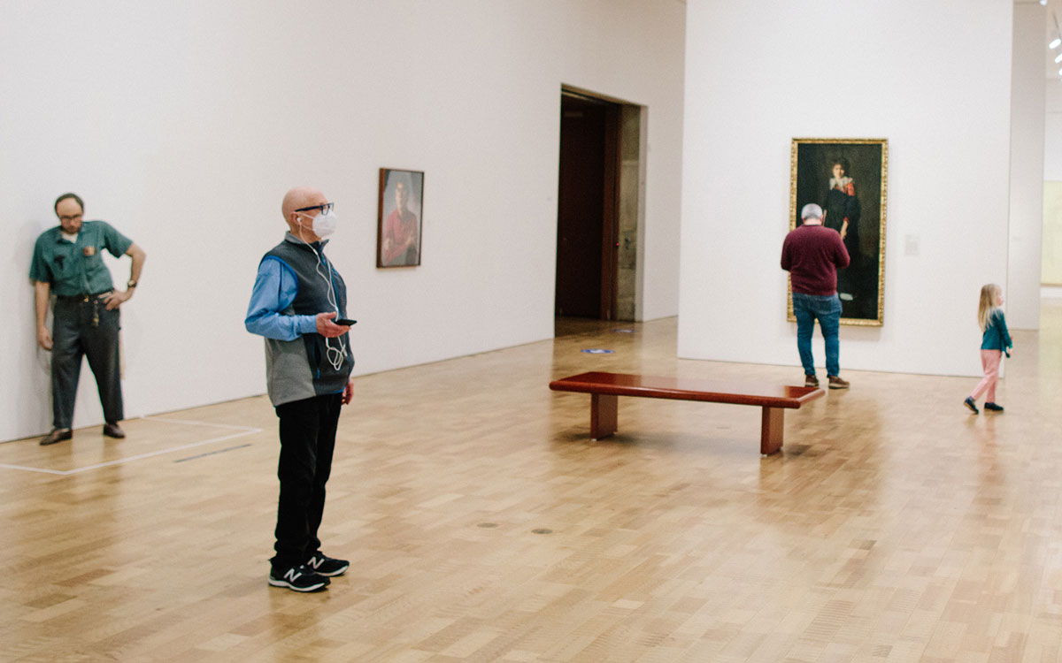 Young boy looking at art while listening to an audio guide