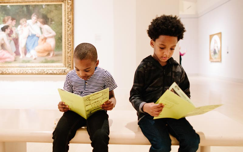 Two young boys reading inside the Museum