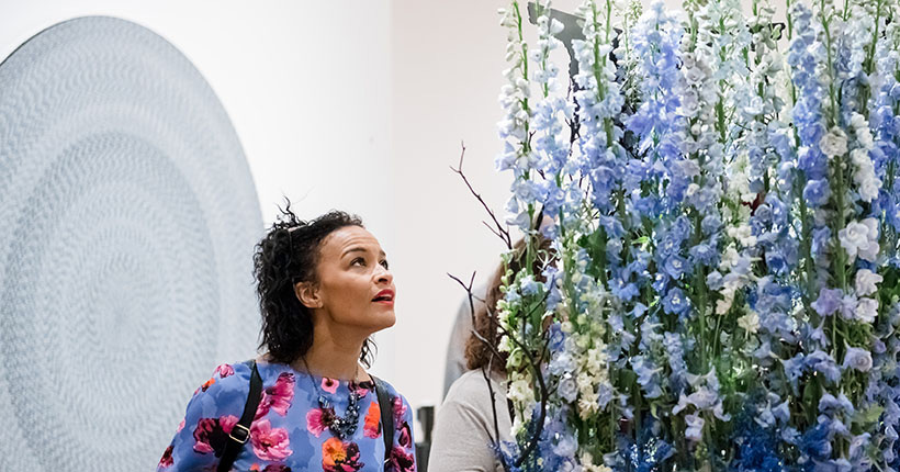 Young woman looking at a floral piece from Art in Bloom