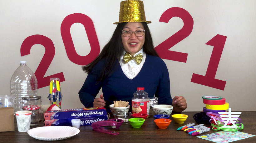 Diane dressed festively for New Year's with a top hat surrounded by supplies like aluminum foil, popsicle sticks, and bowls
