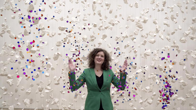 Emily in a green suit in front of white snow-like pieces and confetti