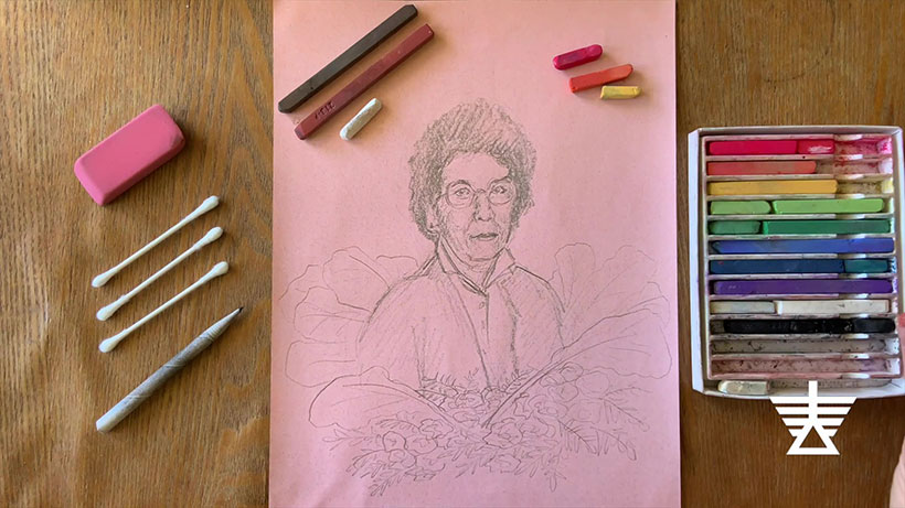 Sketched portrait of a woman on a piece of paper next to pastel-colored chalk