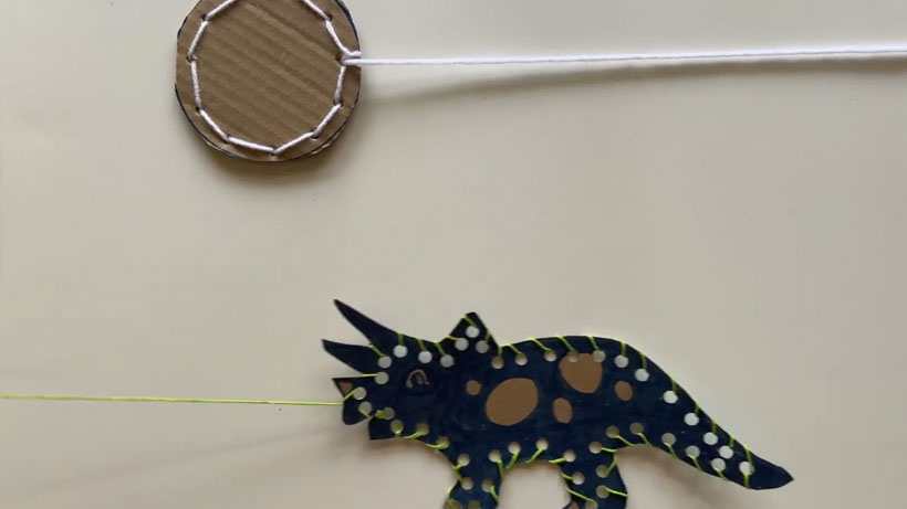 Cardboard Triceratops and sun with yarn stiched around the edges