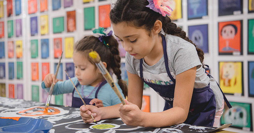 Two children making art for Dia de los Muertos/Day of the Dead