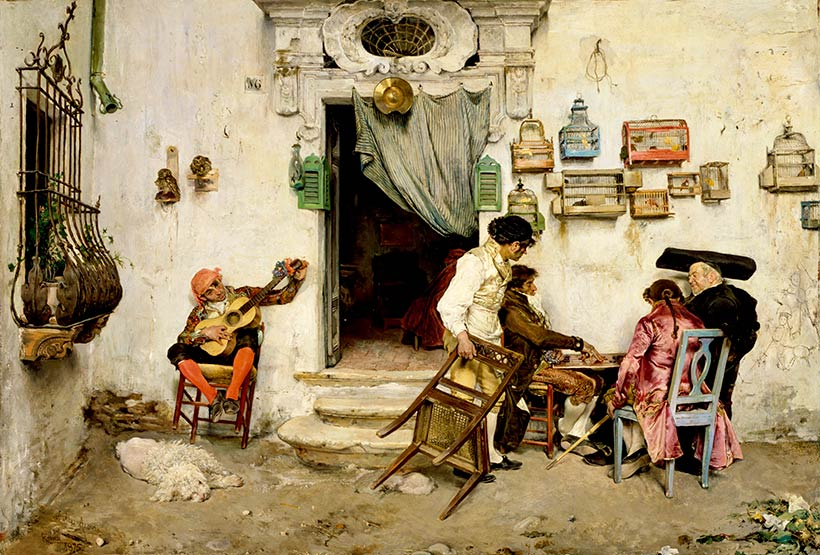 Group of people outside of a shop; one person playing a guitar and three people at a table and a fourth bringing up a chair