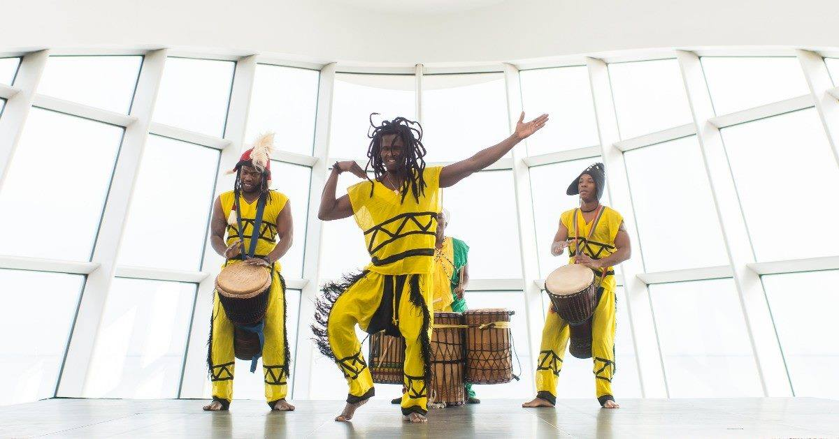 Three men in bright yellow Haitian dress dancing and playing the drums