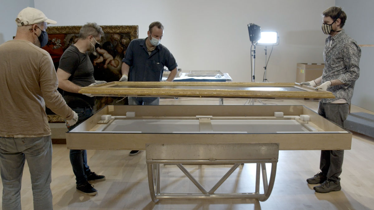 Four men in masks moving a large piece of framed art