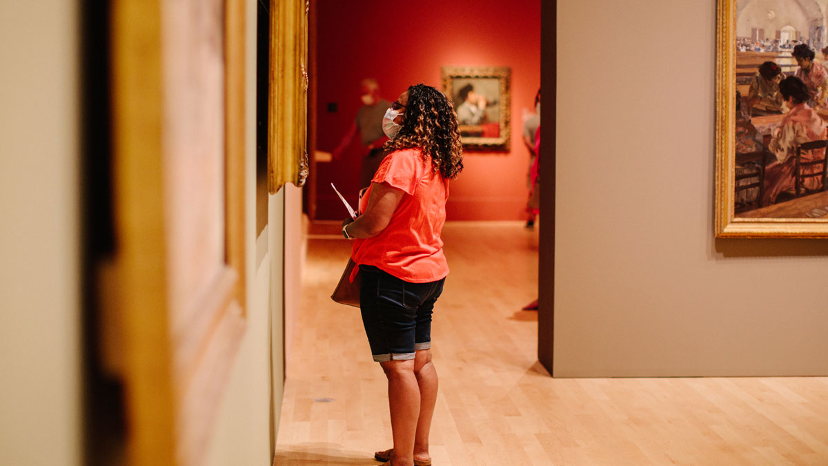 Woman in shorts and a mask looking at art