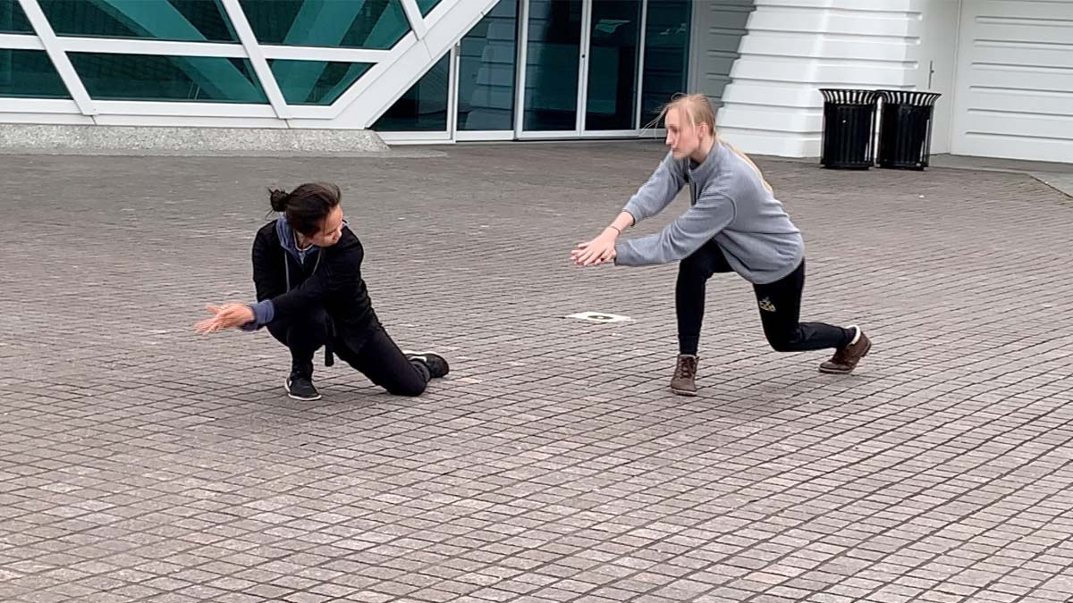 Two dancers from Wild Space Dance Company performing in front of the Museum