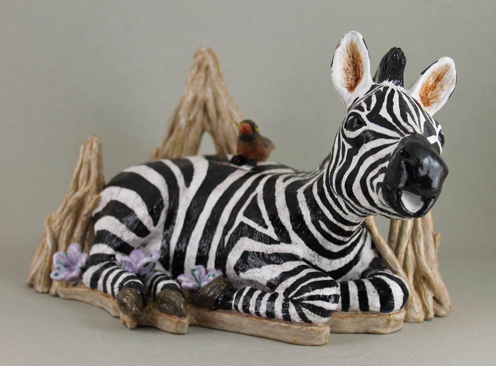Ceramic teapot in the shape of a baby zebra sitting on tree branches with a bird on its back