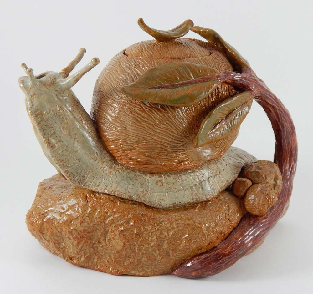 Ceramic teapot in the shape of a snail wrapped in a branch with leaves sitting on a stone