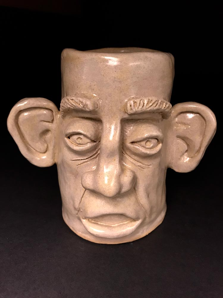 Tan, ceramic sculpture of a face with large ears and nose