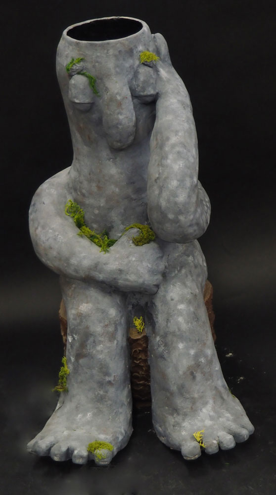 Ceramic vase of a troll sitting on a stump with algae in different places