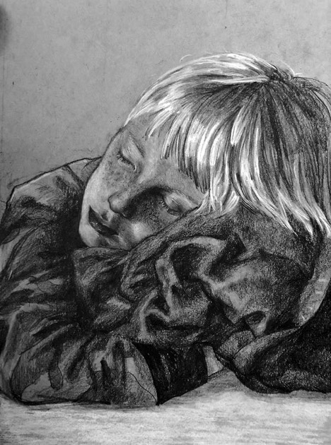 Young boy sleeping and hugging a blanket