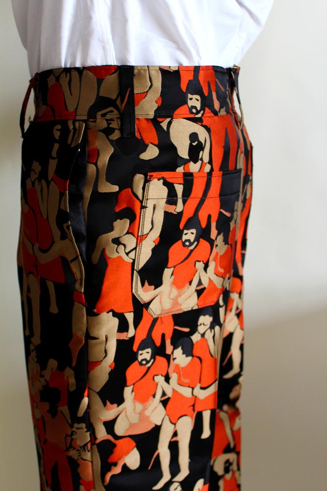 Close up of a pair of orange and black slacks with a pattern of people