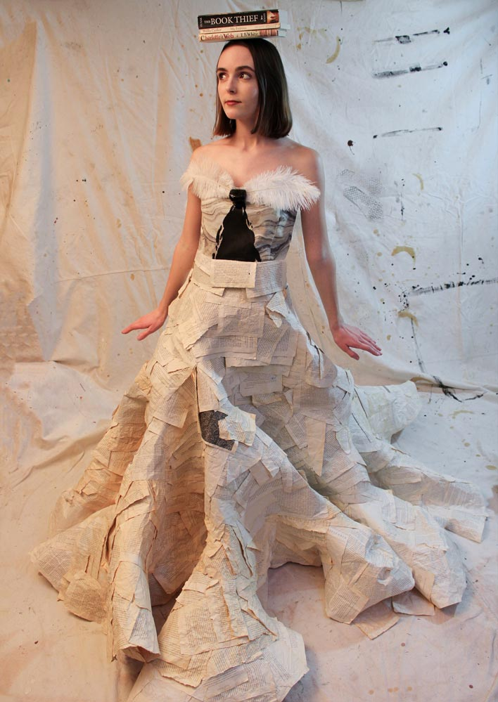 Sleeveless full-length dress made of book pages with feathers at the neckline