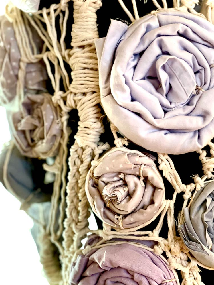 Close up of a top made of twisted and braided rope and cloth roses