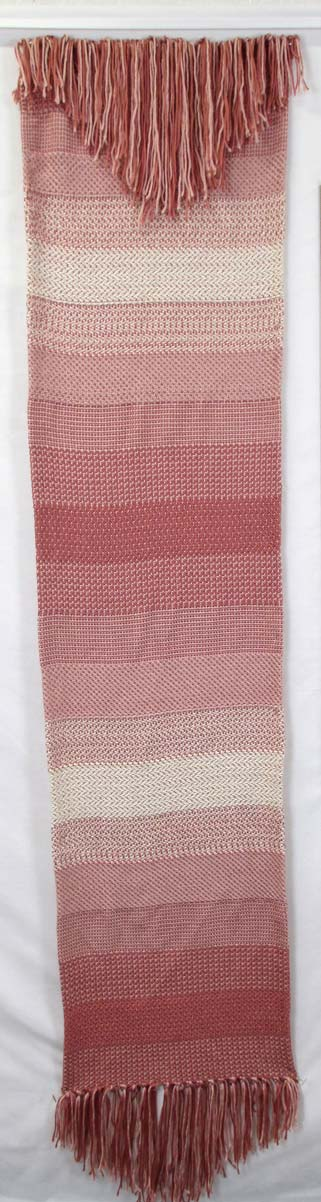 Long woven wall hanging in a pink-toned gradient with frayed ends