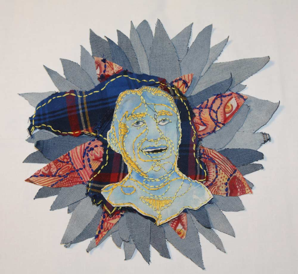 Face with embroidered outlines on top of cut outs in the shape of a flower