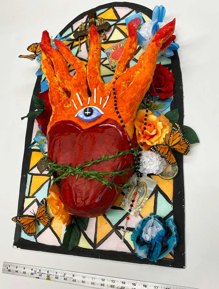 Heart with flames and an eye in the middle in front of a stained glass window with flowers, butterflies, and a rosary