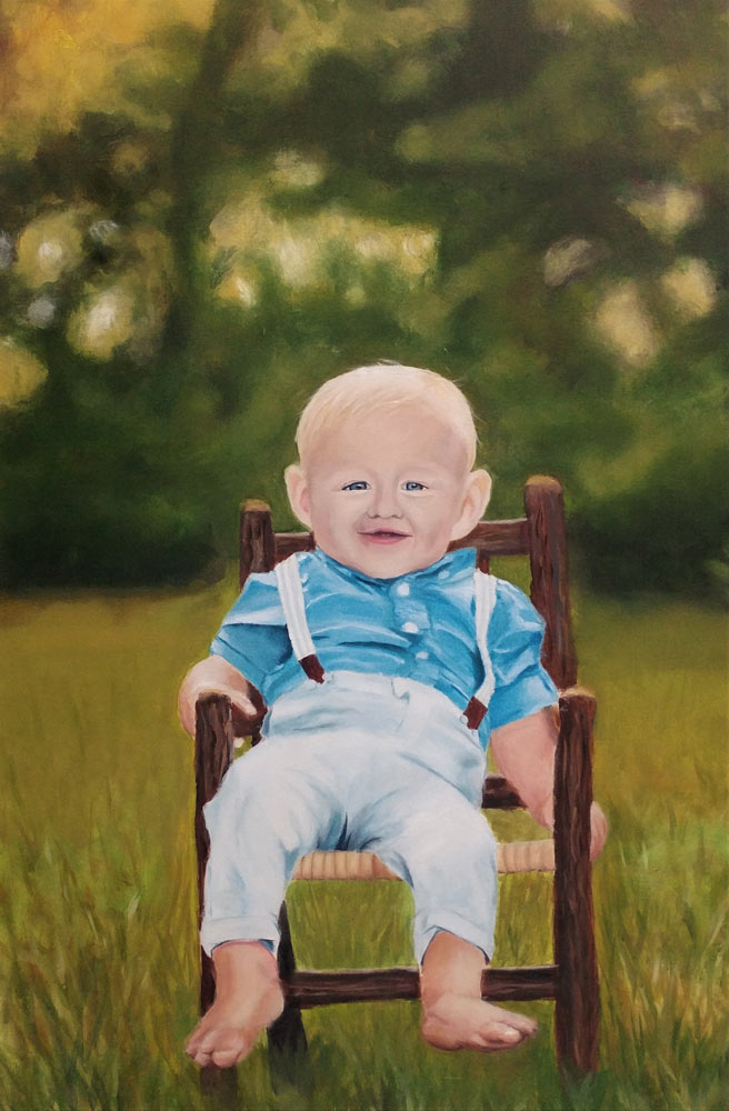 Toddler boy sitting in a wooden chair outside wearing suspenders