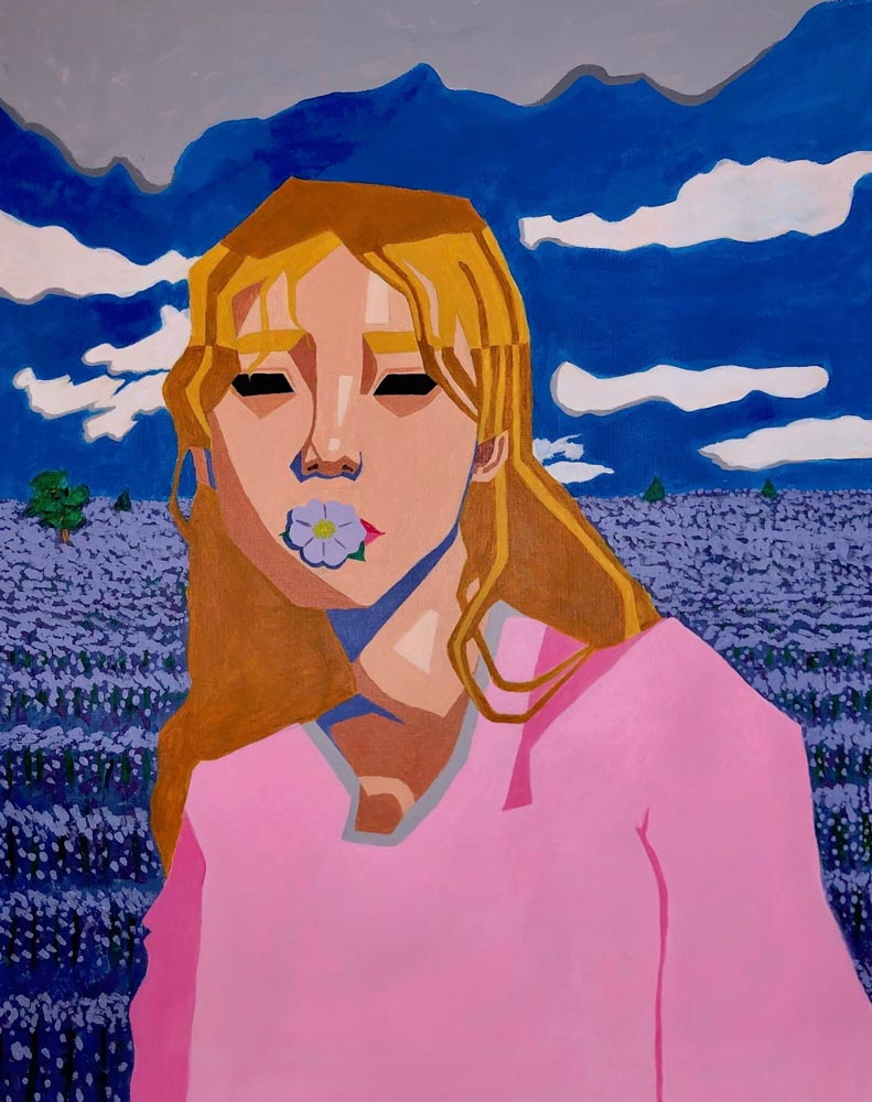 Teen girl in a pink shirt with a flower in her mouth standing in a field with a cloudy blue sky