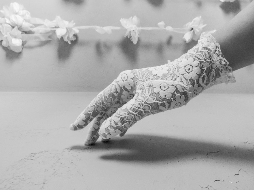 A hand with a white lace glove touching the surface of a table