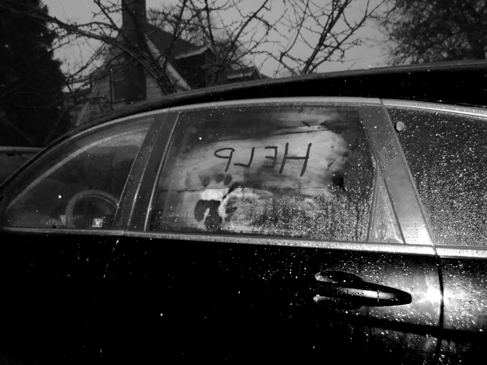 Older black car with help written in the condensation on the window and a handprint