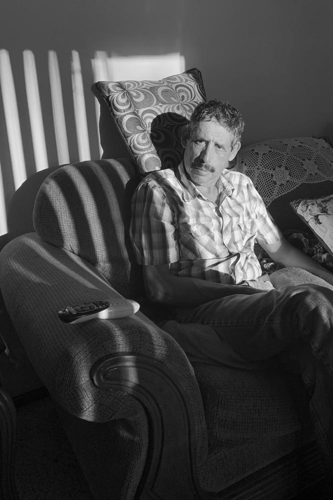 Older man sitting on a couch looking at the camera through a striped shadow