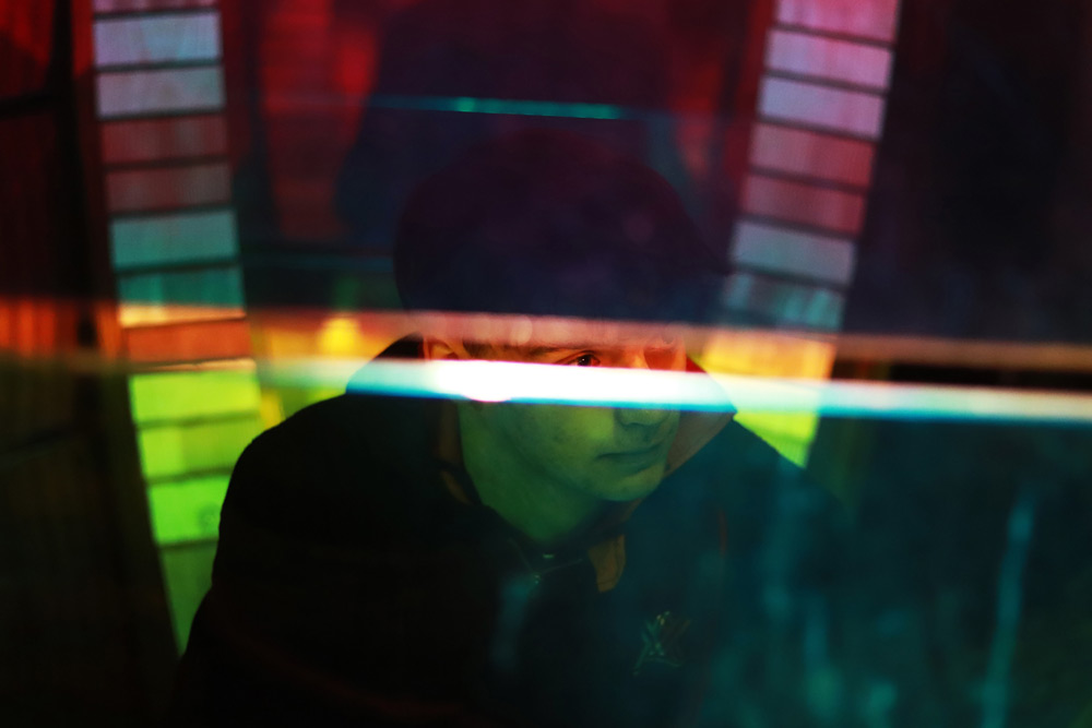 Young man looking to the side behind a transparent wall of colored glass with a crack through the middle