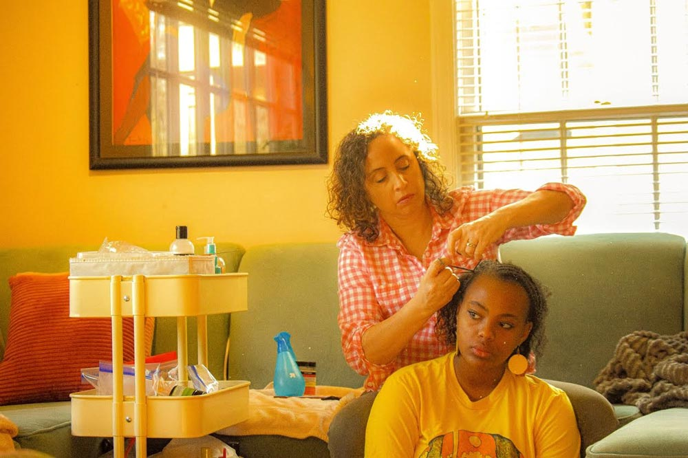 Young woman sitting down while her mother braids her hair