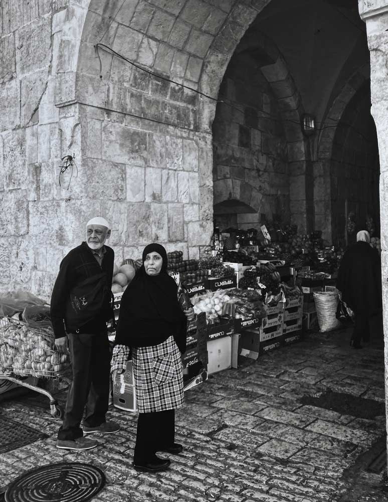Elderly couple standing in an archway surrounded by marketplace goods