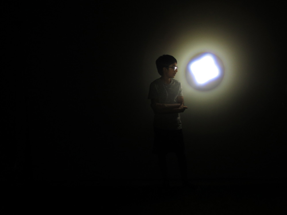Young boy in a pitch dark room with a spotlight shining on him
