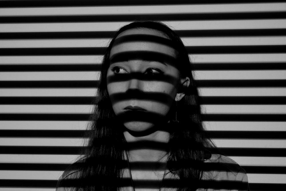 Young woman from the shoulders up with the shadows of blinds on her face