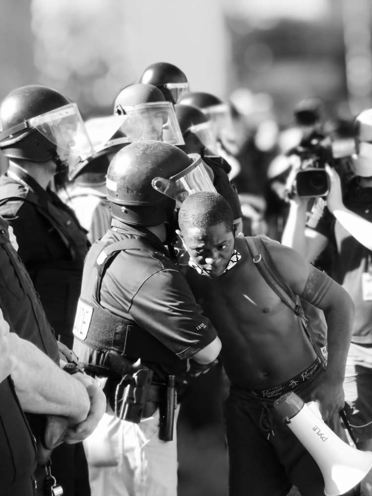 Young man holding a megaphone and locking arms with a police officer in riot gear surrounded by a line of other officers in gear