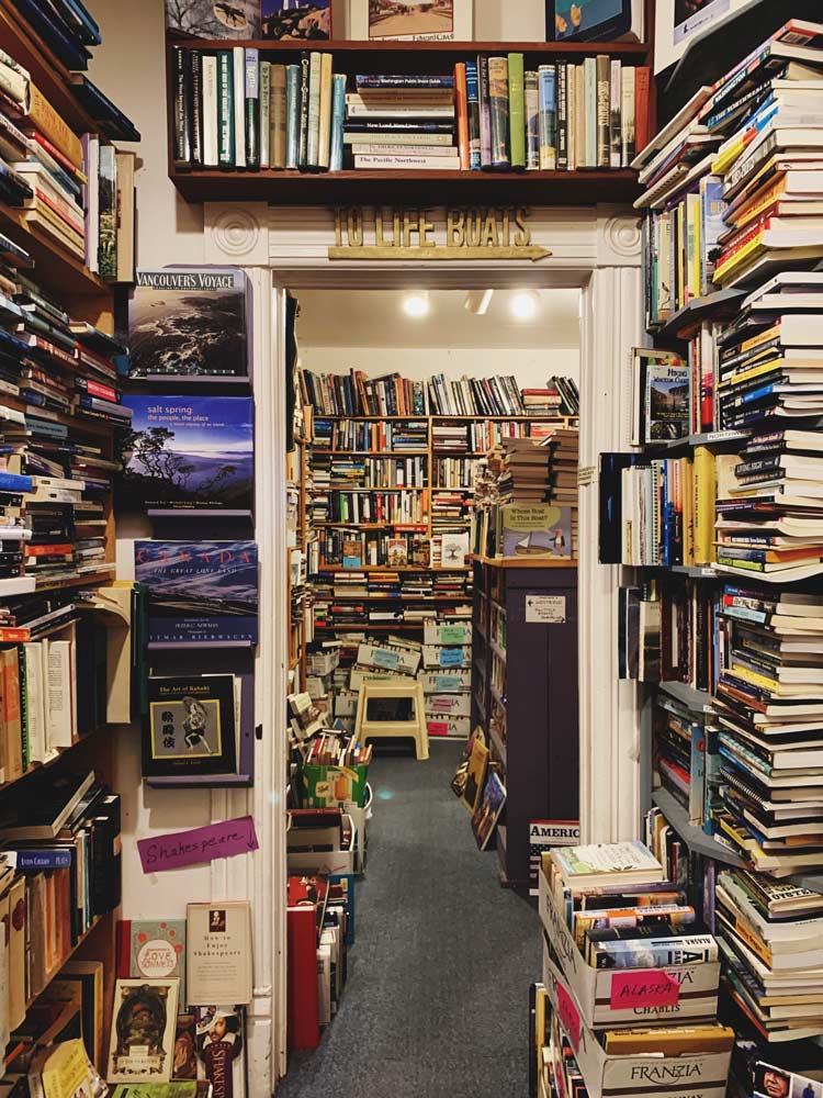 Room surrounded by stacks of books with an archway into another room filled to the ceiling with books