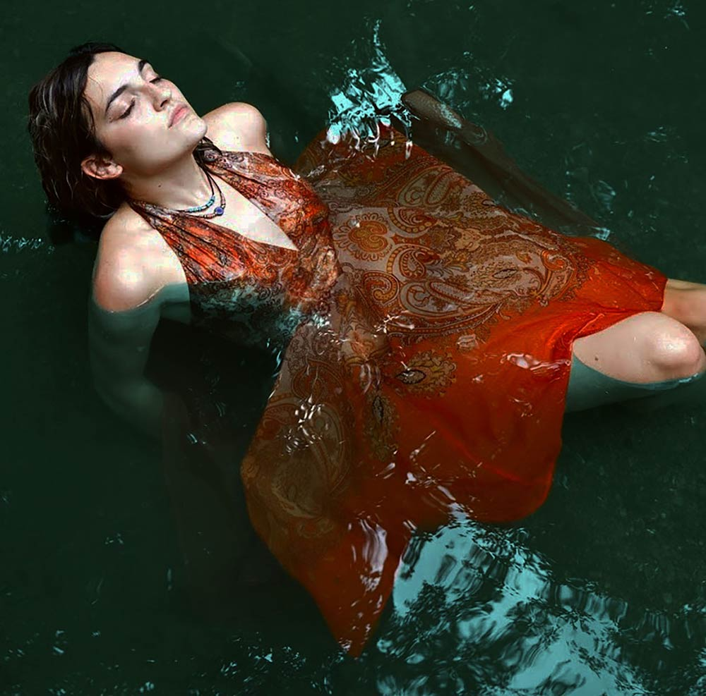 Young woman in a red paisley laying in shallow water with her head back and eyes closed