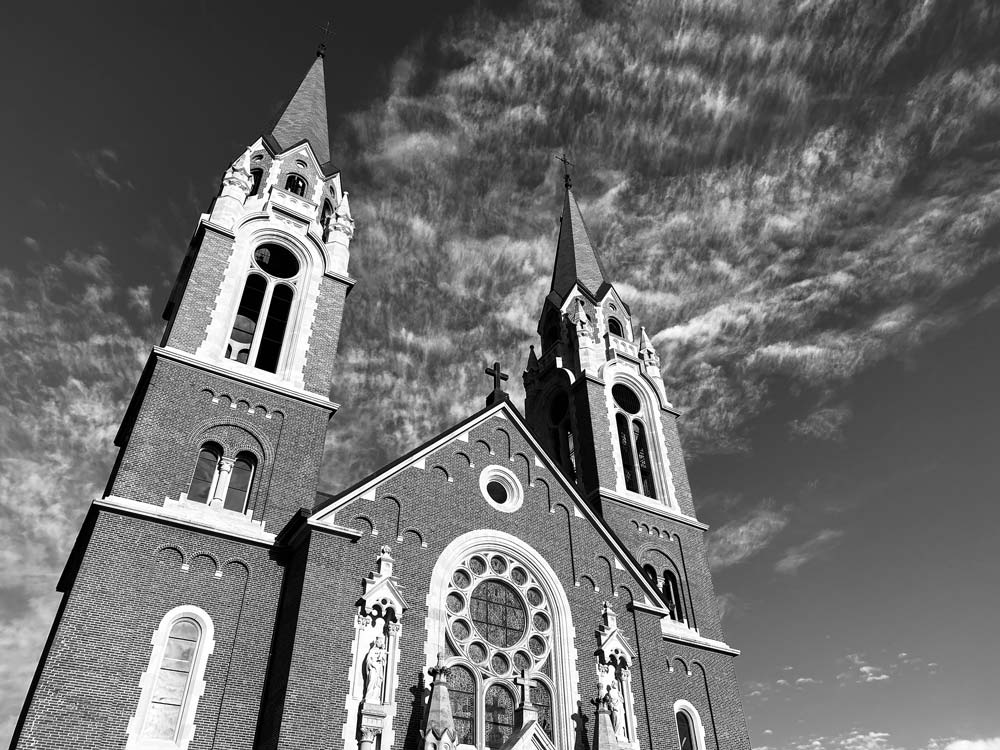 View looking up at a brick church with steeples on each side