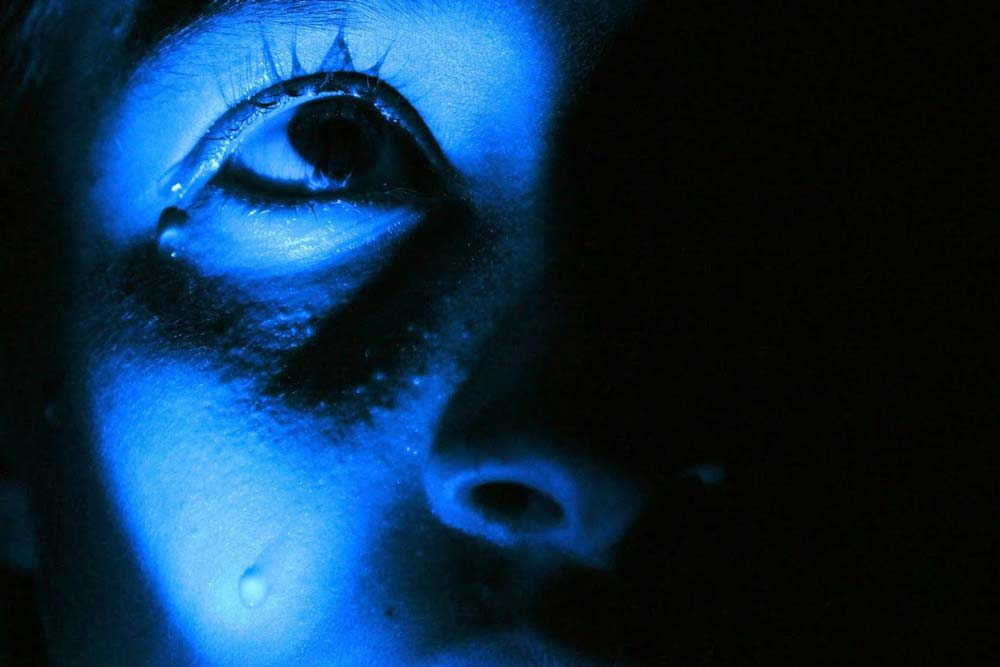 Blue-toned girl zoomed in on an eye with a tear on her cheek