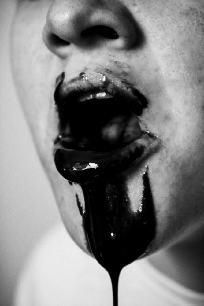 Closeup of a person's open mouth with black liquid dripping out
