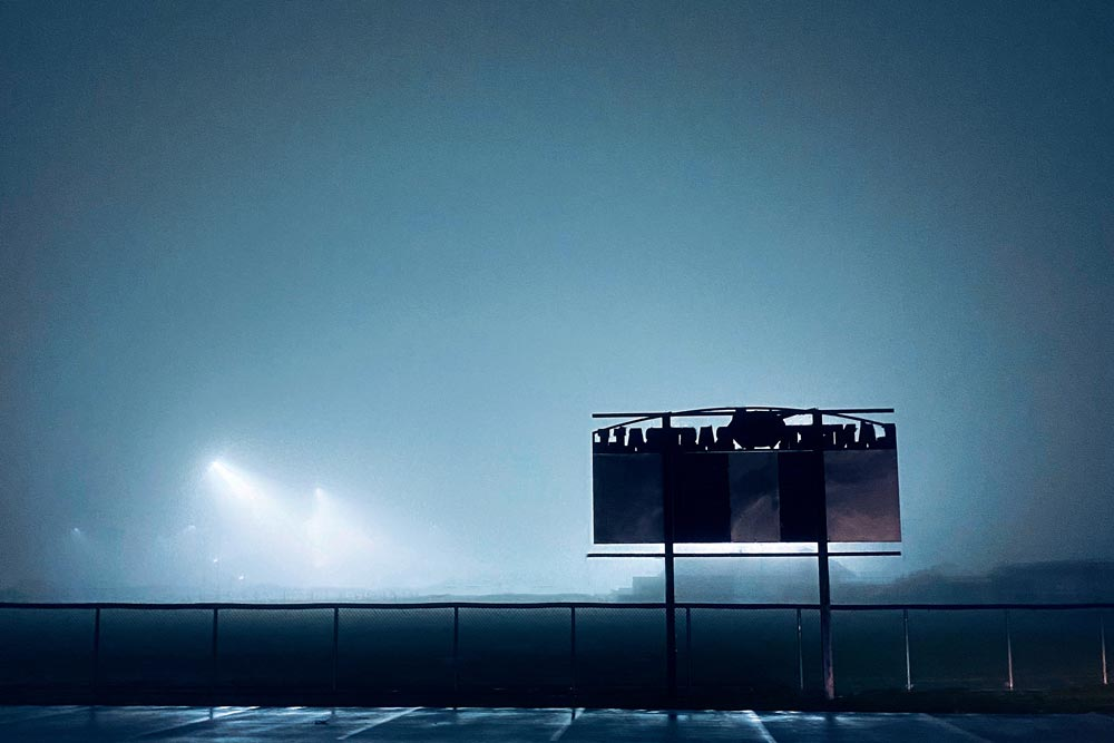 View from a parking lot looking at a school football field at night