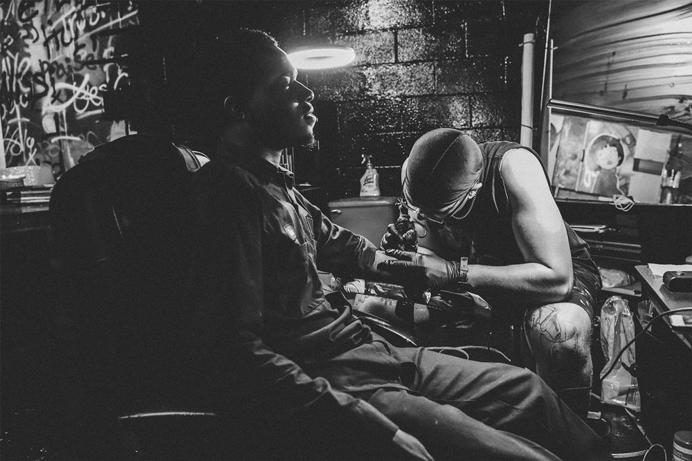 Young man sitting in a chair getting a tattoo