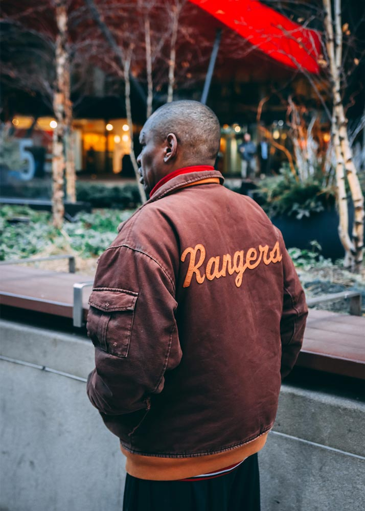 Man walking on the sidewalk wearing a jacket that says Rangers on the back