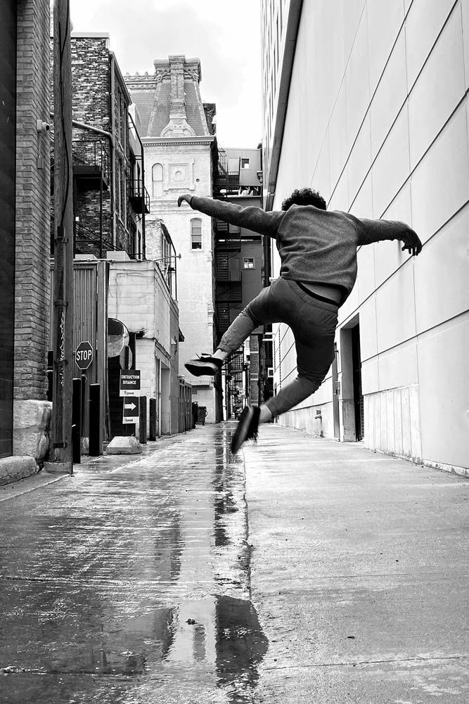 Young man from behind mid-jump in a alley