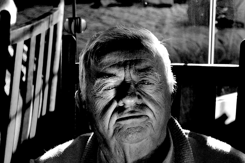 Close-up of an elderly man sitting on a porch swing