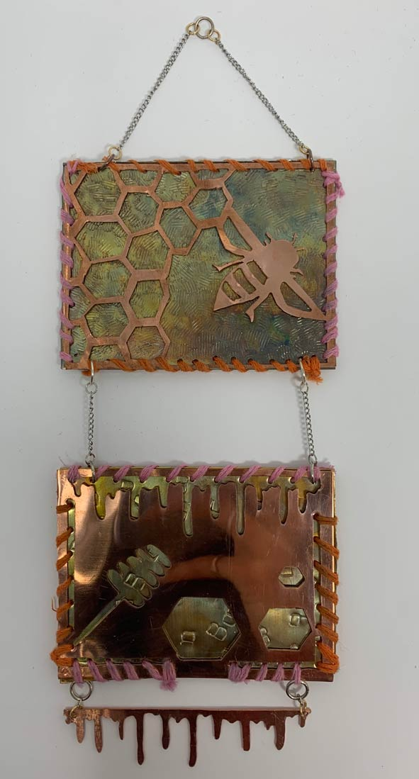 Two pieces of square metal connected together and hanging down, the top designed with a bee and honeycombs and the bottom with a stick of honey