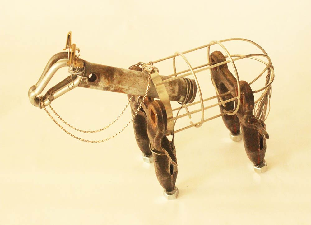 Four-legged sculpture put together with a pipe, carabiners, paper clips, washers, and other pieces of metal